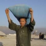 Der er flere internationale organisationer, der uddeler mad i de uofficielle lejre. Her har en dreng fået en sæk ris. Foto: Jens Kjær Jensen, 2003