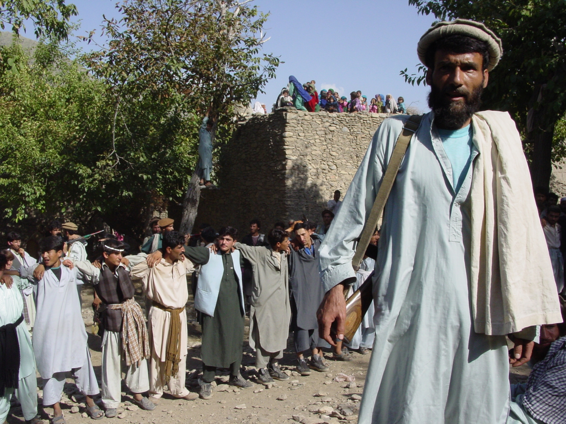 Men and women are segregated during Afghan weddings. Here, the women may be discerned on the roof in the background, from where they can watch the men dancing. The photographer was not allowed into the women's part of the celebrations. Photo: Jens Kjær Jensen, 2003