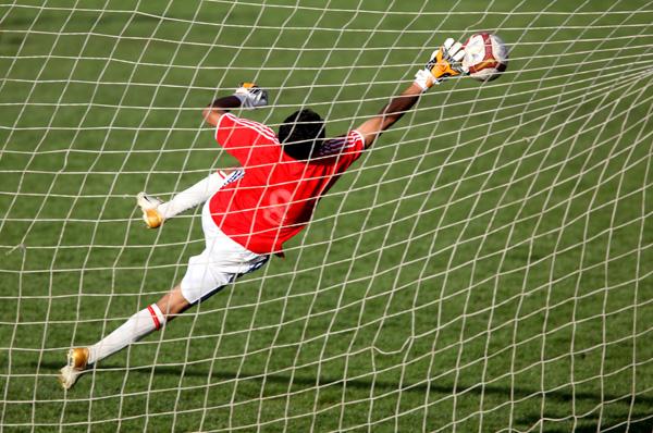 An Afghan goalkeeper reaching for the ball during the 'Ramadan match' on Ghazi Stadium in 2009. Photo: UNAMA/Jawad Jalali