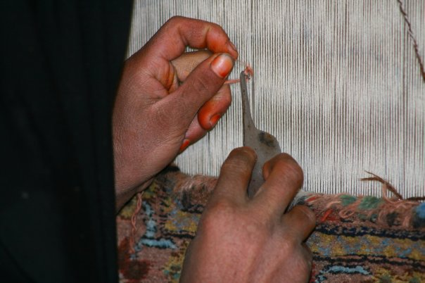 Weaving. The fingers are coloured by henna. Foto: Tahir Bakhtiary, 2013