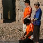 Young men praying before a football match. Photo: Tahir Bakhtiary, 2013