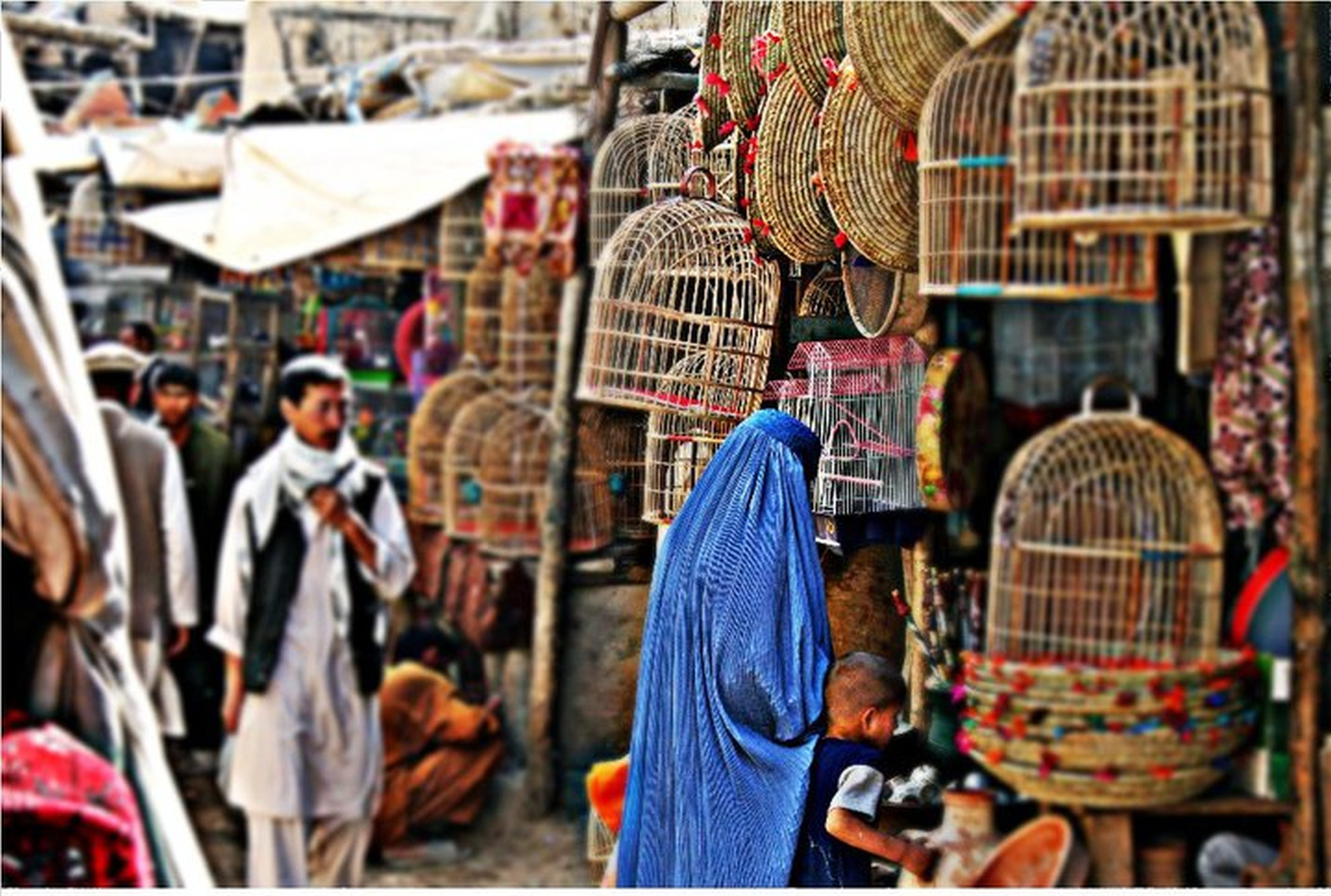 A woman looks a birdcages in Kabul. It is popular to keep birds as pets in Afghanistan. Photo: Tahir Bakhtiary, 2013