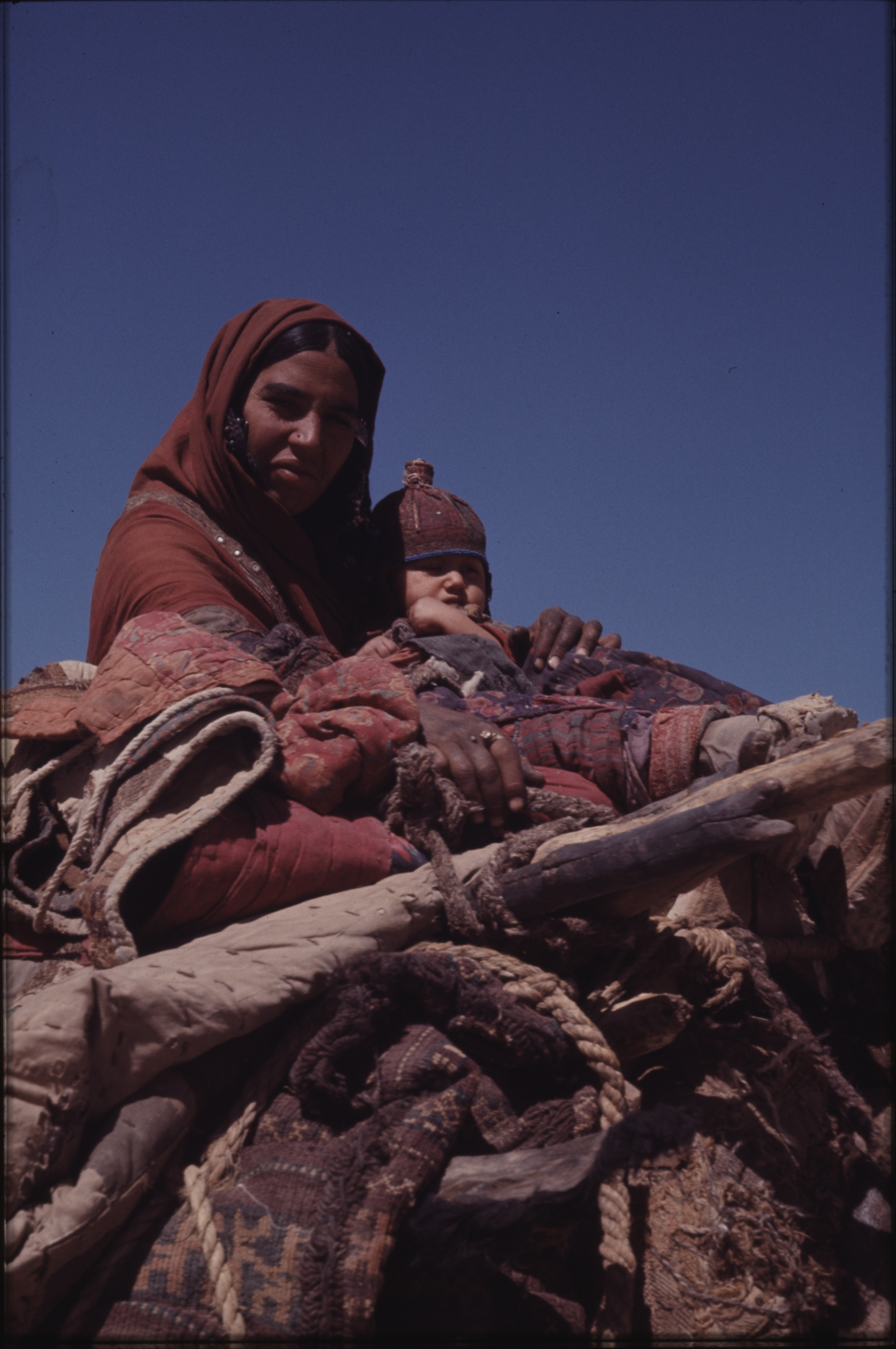 Roughly half the children die within the first few years of life. No medical care is available. Here a mother and daughter on a camel, heading for the mountains. Photo: Jean Bourgeois, 1971