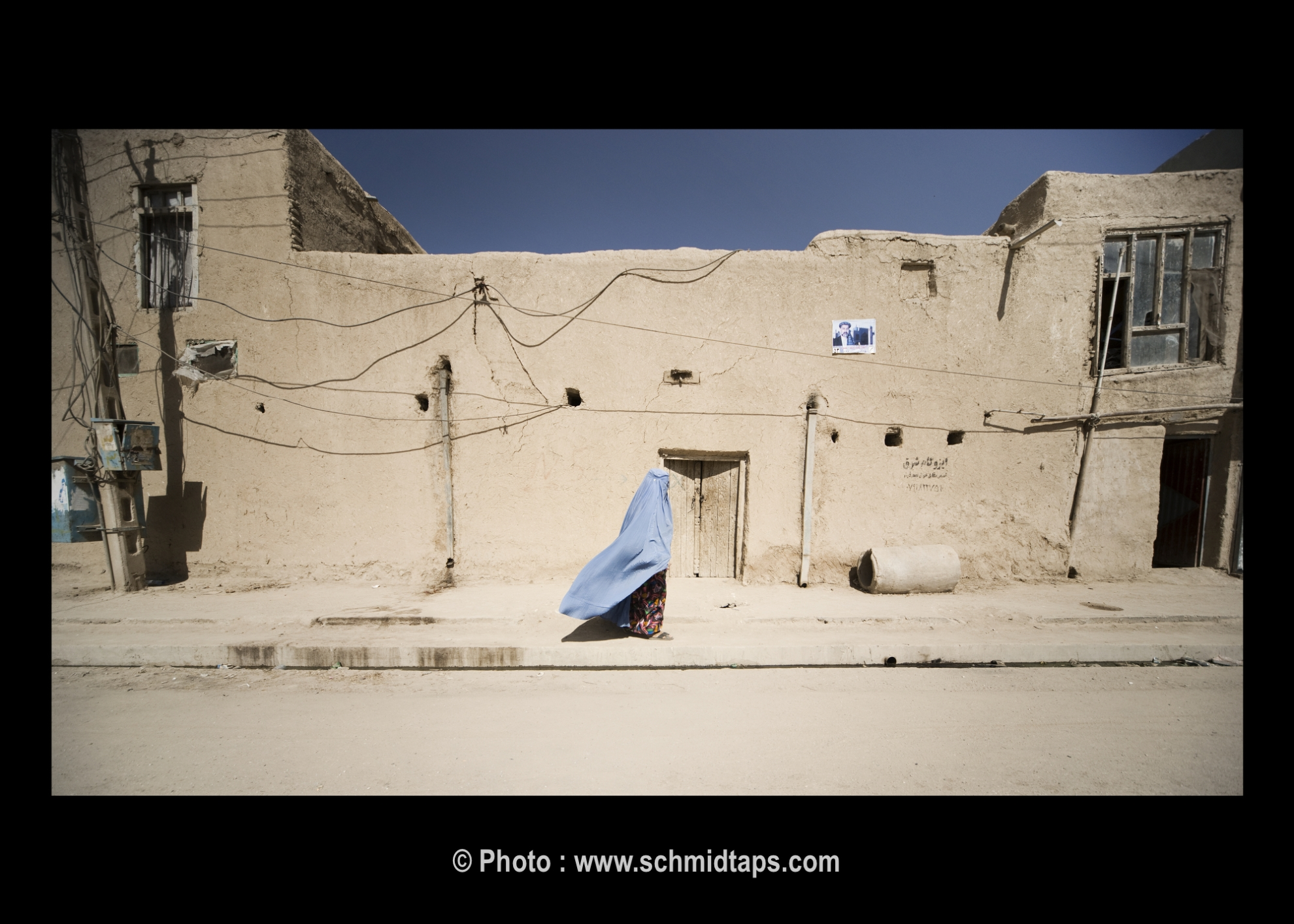 The blue burqa creates a beautiful contrast to the mud walls of the houses. Photo: Lars Schmidt, 2010-'13